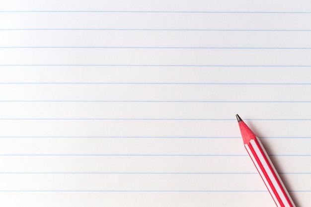Красный полосатый карандаш на белом фоне пустой бумаги выложены ноутбука с копией пространства. обратно в школу, образование, концепция обучения