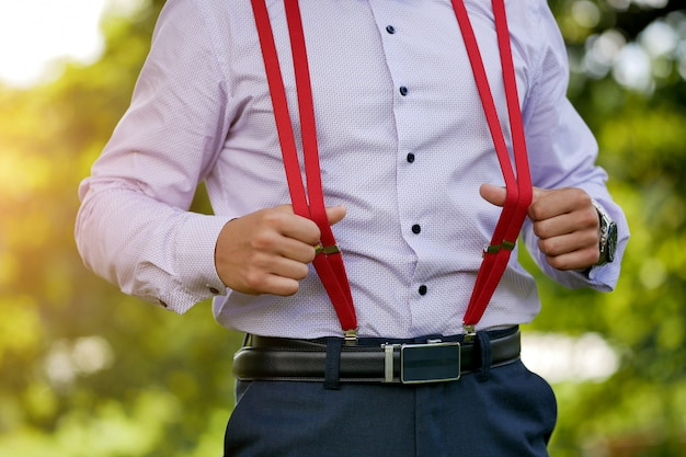 Red stylish men's suspenders on blue shirt