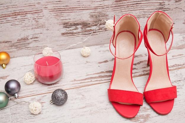木製の背景、毛皮ツリーの飾り、キャンドルに赤いスエードの靴