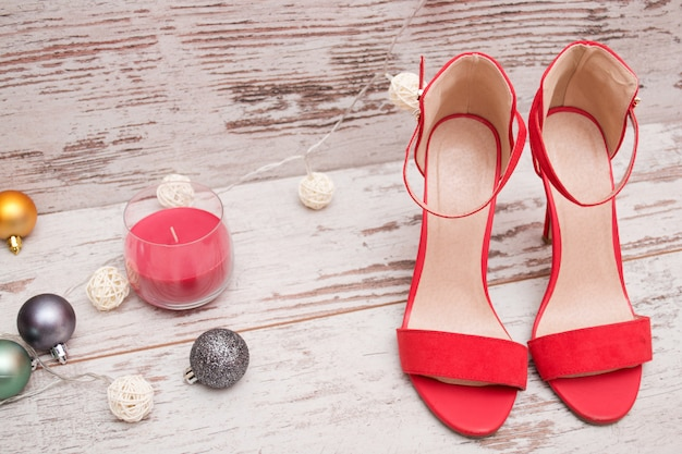 Red suede shoes on a wooden background, fur-tree ornaments and candle