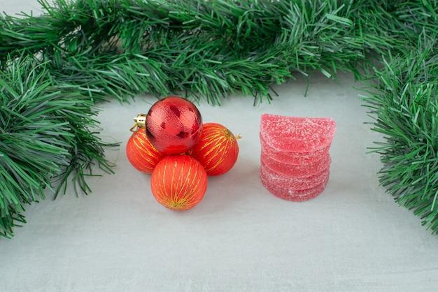 大理石の背景に赤いクリスマスボールと赤い砂糖マーマレード。高品質の写真