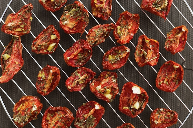 Red sun-dried tomatoes with garlic and provencal herbs on metal grid