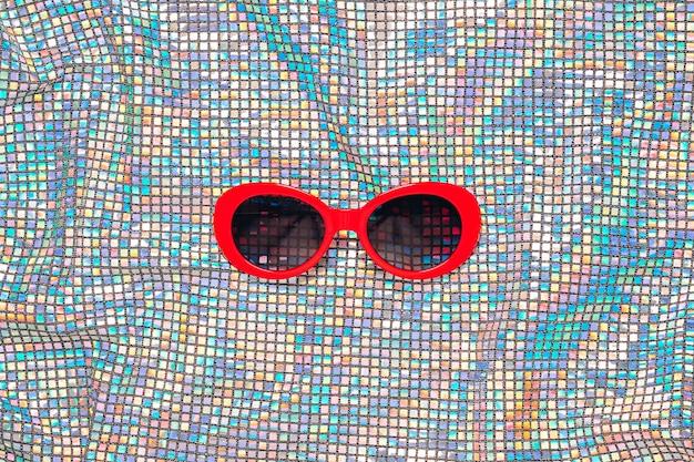 Красные солнцезащитные очки на текстуре радуги.