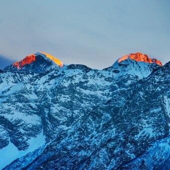 Красный закат в горах, покрытых снегом.