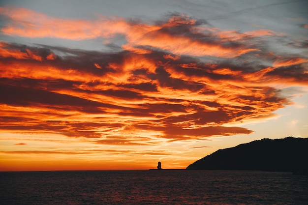 Red sunset sky in the coast of barcelona and a lighthouse at the background