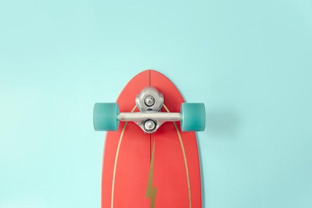 Красный серфинг скейт или скейтборд на синем цветном фоне