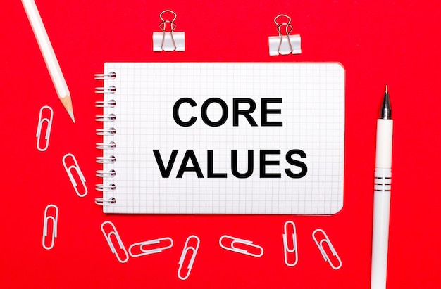 On a red surface, a white pen, white paper clips, a white pencil and a notebook with the text core values