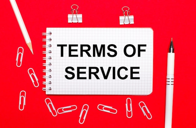 On a red surface, a white pen, white paper clips, a white pencil and a notebook with the text terms of service. view from above