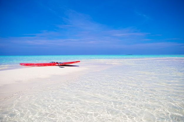 Red surfboard on white sandy beach with turquoise water at tropical island in indian ocean