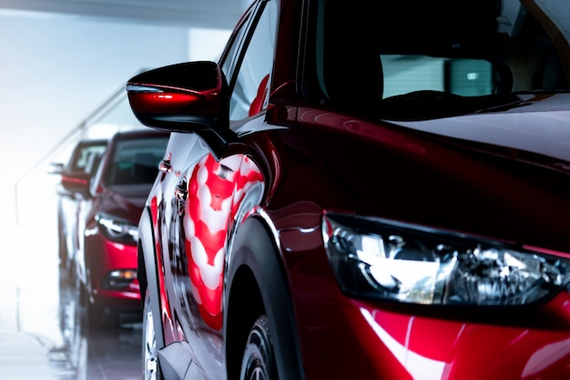 Red suv car parked in modern showroom. new and luxury suv compact car. car dealership concept. automotive industry. automobile leasing business. front view of red shiny car parked in showroom.