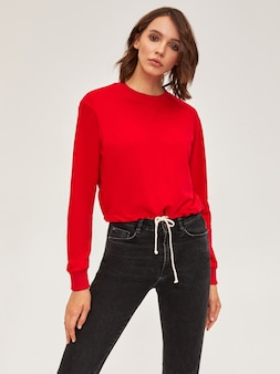 ブルネットの短い髪のモダンなスリムな女の子に赤いセーターと黒のスキニージーンズ。白い背景の上のスタジオに立っています。
