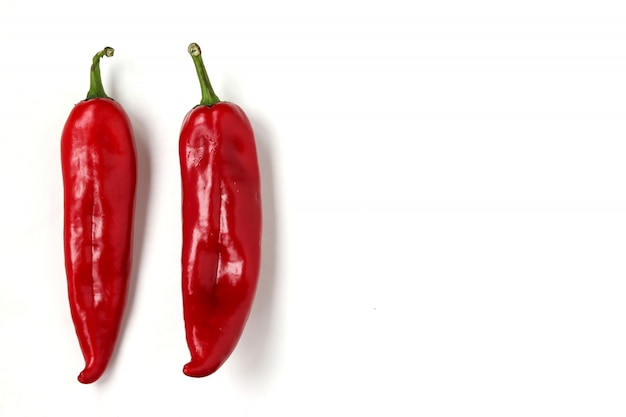 Red sweet pepper is located on a white surface, copy space
