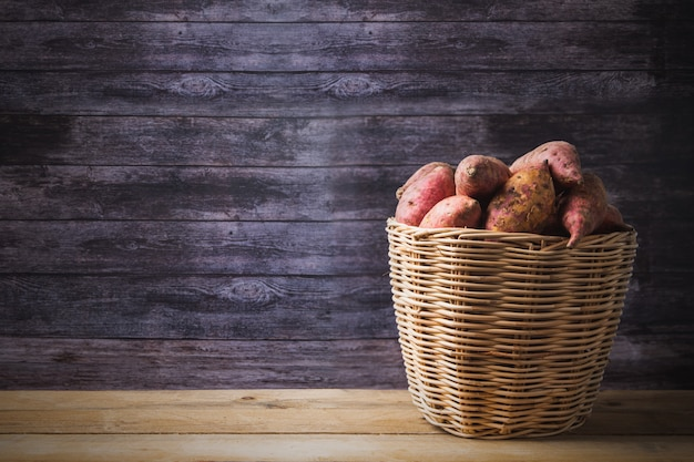 Red sweet potatoes in basket,  raw food display on wooden table background with copy space