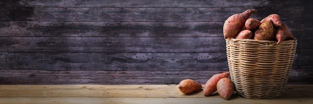 바구니에 붉은 고구마, 복사 공간 나무 테이블 배경에 날 음식 표시