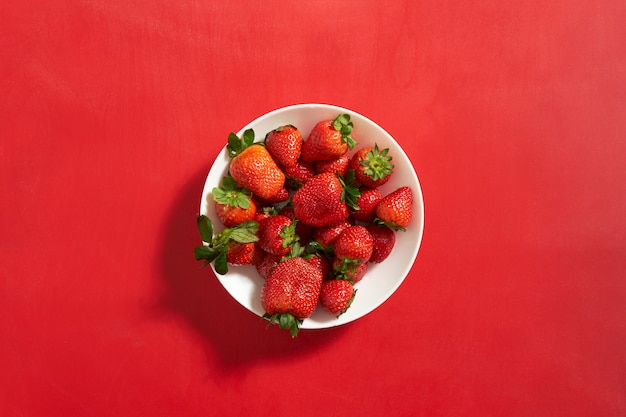 Red sweet ripe strawberries in a white plate on red wall background