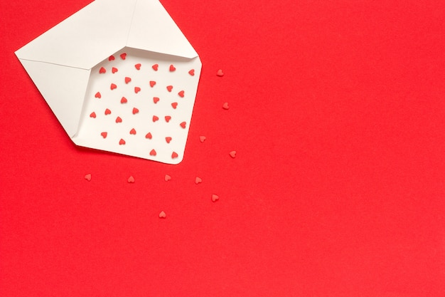 Red sweets sprinkles candy hearts fly out of white paper envelope on red background.