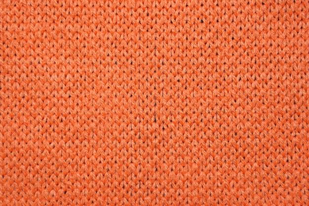 赤い合成繊維のニット生地をクローズアップ。ニット生地のテクスチャ背景