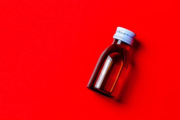 Red syrup medicine in clear bottle on red background