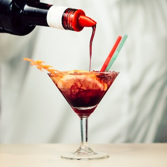 Red syrup pouring into tropical cocktail