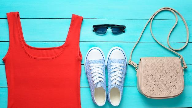 Красная футболка, кроссовки, кожаная сумка, солнцезащитные очки на синем деревянном столе.
