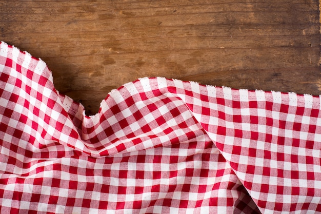 Red table cloth on wooden background