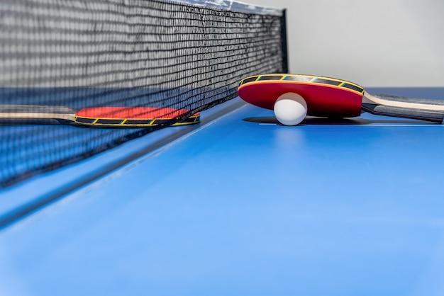 검은 그물이 있는 파란색 탁구대에 빨간색 탁구 라켓과 흰색 공, 두 개의 탁구 패들은 스포츠 경기 장비 실내 활동 및 개념 배경 운동입니다.