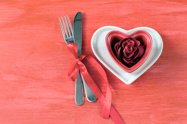 On a red table two heart-shaped plates, a red rosebud, and cutlery tied with a red ribbon