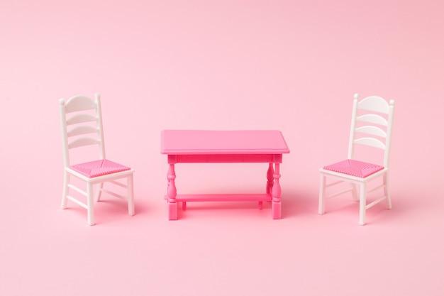 ピンクの表面に2つの椅子が付いた赤いテーブル