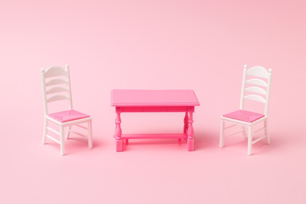 Red table with two chairs on a pink surface