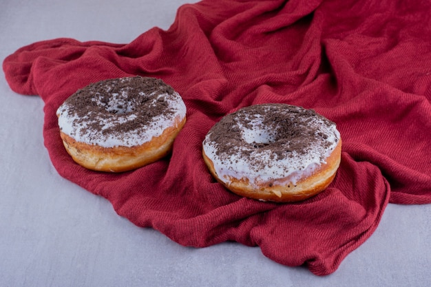 Red tablecloth under donuts on white background.