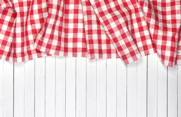 Red tablecloth on white wooden table, top view