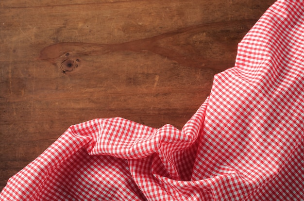 Red tablecloth on wooden table background