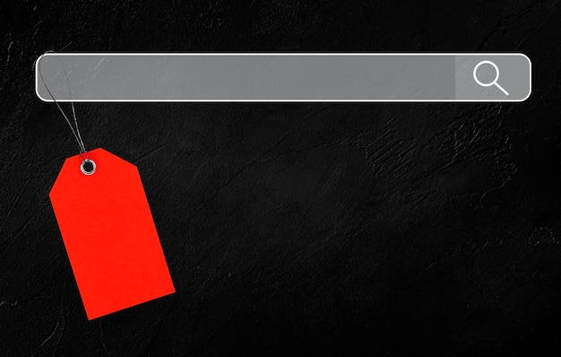黒いコンクリートの背景の検索エンジンにぶら下がっている赤いタグ