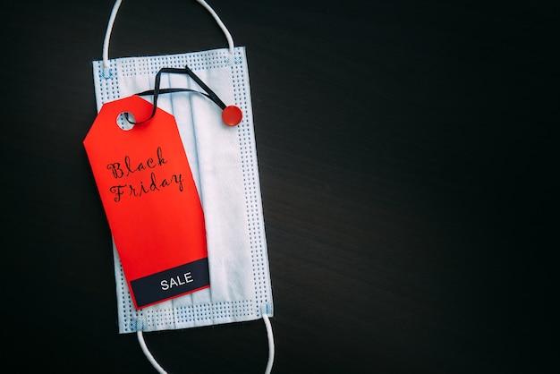Красная бирка с надписью черная пятница на фоне медицинской маски. продажи в контексте пандемии covid-19. концепция безопасных покупок.