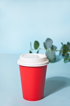 Red take away coffee cup and home plant