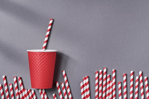 Красная кружка кофе на вынос с бумажной трубочкой для питья на серой таблице цветов тенденции. нулевые отходы, концепция устойчивого образа жизни. вид сверху с копией пространства