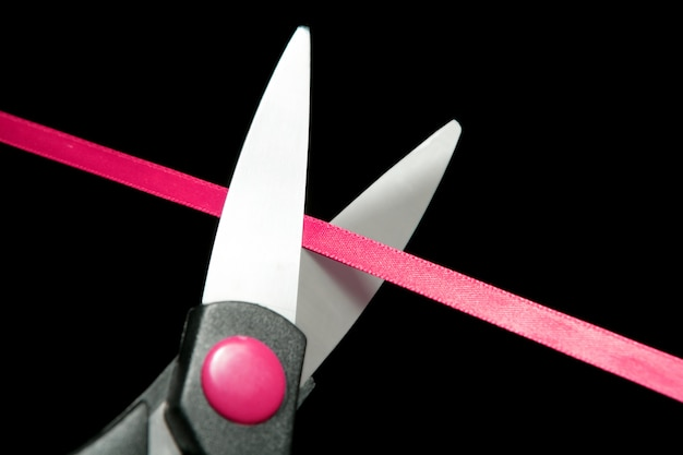 Red tape going to be cutted by scissors