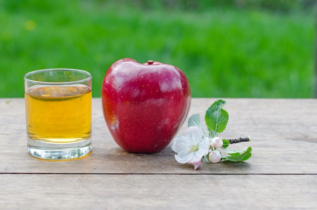Red and tasty apples with a glass of cider (apple juice) on wooden table