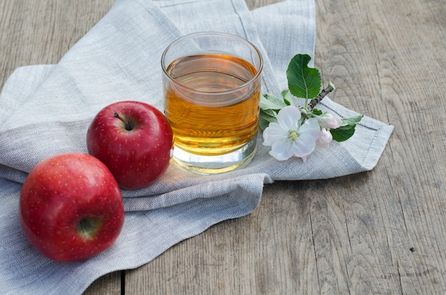 Red and tasty apples with a glass of cider (apple juice)