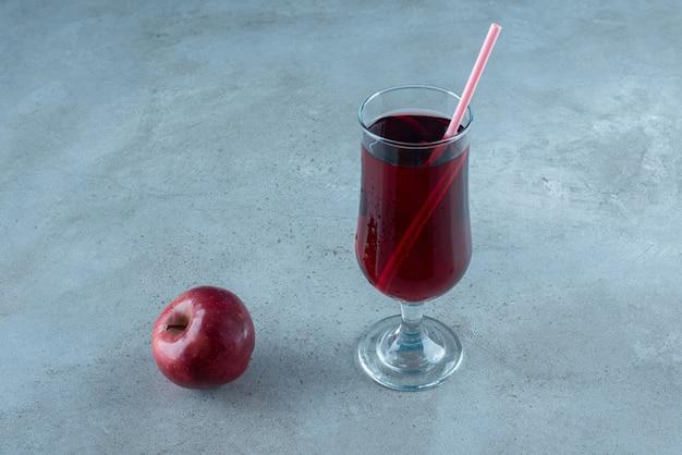 Красный вкусный сок со свежим яблоком и соломой.