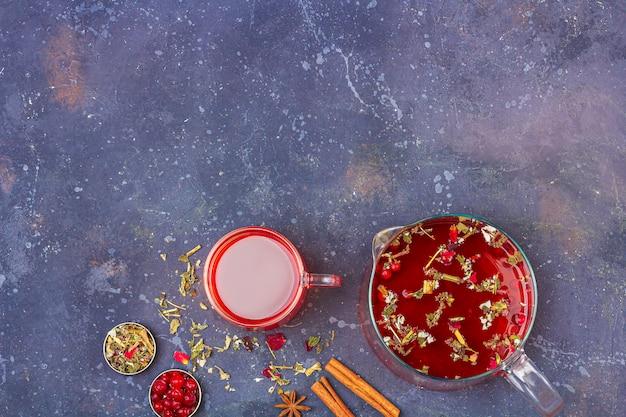 暗い背景にシナモン、アニス、クランベリーの中でティーポットとガラスのコップの赤茶。風邪やインフルエンザのためのハーブ、ビタミン、デトックスティー。