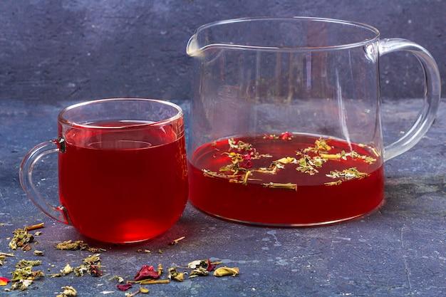 乾燥茶葉と花びらの中でガラスカップとティーポットの赤茶