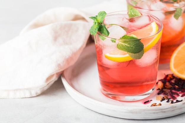 Красный чай каркаде игристый холодный в бокалах с мятой и лимоном