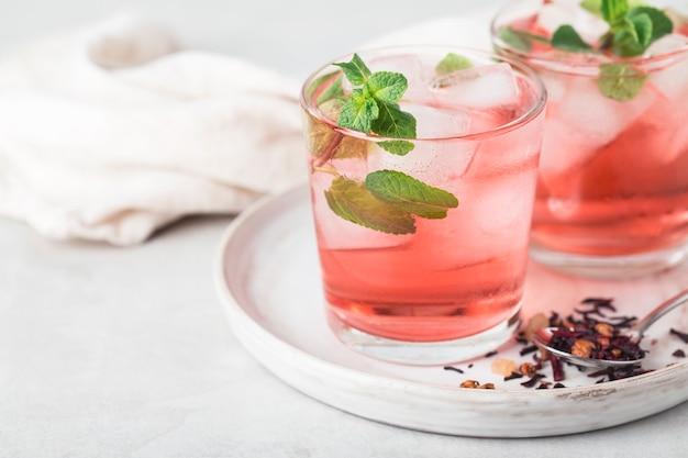 Красный чай каркаде игристый холодный в бокалах с мятой