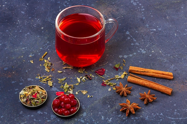 Red tea (rooibos, hibiscus, karkade) in glass cup and teapot among cinnamon, anise, cranberries on a dark background. herbal, vitamin, detox tea for cold and flu. close up, copy space for text