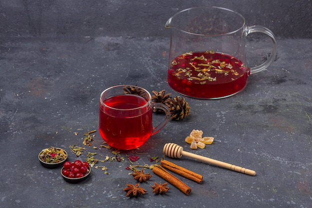 Red tea (rooibos, hibiscus, karkade) in glass cup and teapot among cinnamon