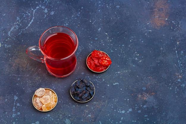 ハナミズキ、レーズン、暗い背景にオリエンタルスタイルの砂糖とトルコのティーカップ(armudu)の赤茶(ルイボス、ハイビスカス、カルカデ)。風邪やインフルエンザのためのハーブ、ビタミン、デトックスティー。テキスト用のコピースペース
