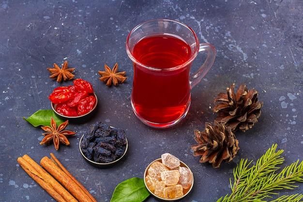 ハナミズキ、レーズン、暗い背景にオリエンタルスタイルの砂糖とトルコのティーカップ(armudu)の赤茶(ルイボス、ハイビスカス、カルカデ)。風邪やインフルエンザのためのハーブ、ビタミン、デトックスティー
