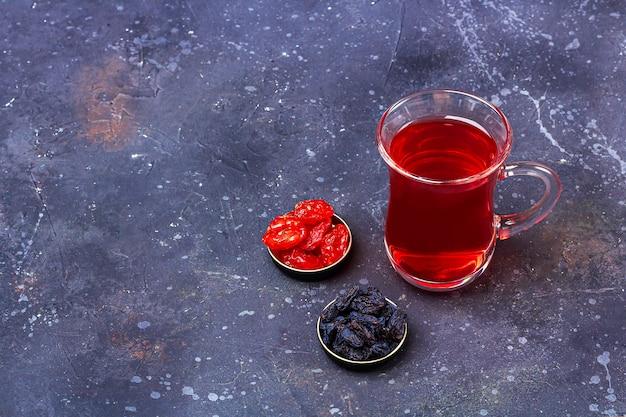 暗い背景にオリエンタルスタイルのドライフルーツ(ハナミズキ)とトルコティーカップ(armudu)の赤茶(ルイボス、ハイビスカス、カルカデ)。風邪やインフルエンザのためのハーブ、ビタミン、デトックスティー。閉じる、