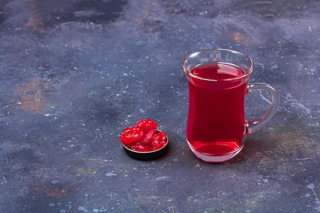 暗い背景にオリエンタルスタイルのドライフルーツ(ハナミズキ)とトルコティーカップ(armudu)の赤茶(ルイボス、ハイビスカス、カルカデ)。風邪やインフルエンザのためのハーブ、ビタミン、デトックスティー。